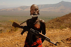 Young Mursi woman with clay plate in lower lip, holding her Kalashnikov rifle (result of the cold war in Africa), Omo valley, Ethiopia, 2006  -  Laurent Geslin