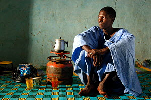 Fulani man brewing tea on calor gas in his house wearing traditional Mauritanian costume, South Mauritania, West Africa, 2005  -  Laurent Geslin