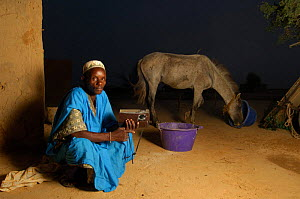 Fulani man listening to radio with horse in background, South Mauritania, West Africa, 2005  -  Laurent Geslin