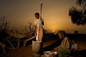 Young Fulani girls grinding seed for flour at dawn, North Senegal, West Africa, 2005  -  Laurent Geslin