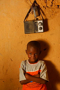 Fulani child sitting beside radio and mobile telephone, portrait, North Senegal, West Africa, 2005  -  Laurent Geslin