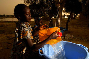 Young Fulani women drawing water from a well shaft built by the United Nations High Commision for Refugees, North Senegal, West Africa, 2005  -  Laurent Geslin