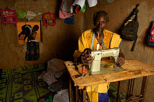 Fulani man with sewing machine, making traditional costumes to sell at market, South Mauritania, West Africa, 2005 - Laurent Geslin