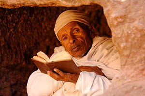Christian worshipper near St Sauveur's church, Lalibela, North Ethiopia. These worshippers stay for hours in a hole in the carved rock to read their holy books. 2006  -  Laurent Geslin