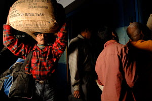 Man carrying sack of tea on his head at Bharatpur railway station, Rajasthan, India 2006 - Laurent Geslin