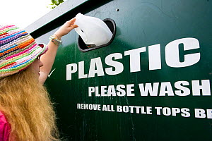 Woman putting plastic bottle into recycling unit in supermarket carpark, Shrewsbury, Shropshire, UK  -  Ben Osborne