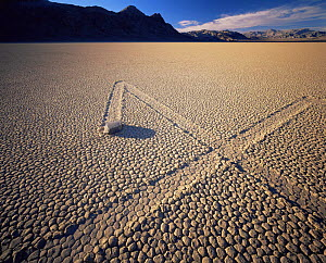 Boulder with zig-zag trails across a dry lake bed, sunset, Ubehebe Peak in distance, The Racetrack Playa, Death Valley National Park, California  -  Jack Dykinga