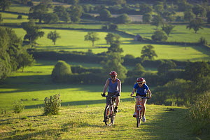 Man and woman on mountain bikes cycling on Hambledon Hill above the Blackmore Vale, Dorset, England, UK  -  David Noton
