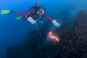 Diver Bud Turpin observes erupting pillow lava at ocean entry of Kilauea Volcano on Hawaii Island, Hawaii. Model released MR 381 - Doug Perrine