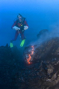 Diver Bud Turpin observes erupting pillow lava at ocean entry of Kilauea Volcano on Hawaii Island, Hawaii. Heat waves rising from the lava distort his image. Model released MR 381 - Doug Perrine