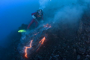 Diver Bud Turpin observes erupting pillow lava at ocean entry of Kilauea Volcano on Hawaii Island, Hawaii,  Heat waves rising from the lava distort his image. Model released MR 381 - Doug Perrine