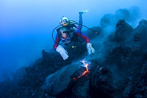 Diver Bud Turpin observes erupting pillow lava at ocean entry of Kilauea Volcano on Hawaii Island, Hawaii. Heat waves rising from the lava distort his image Model released MR 381 - Doug Perrine