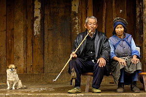 Naxi woman with man smoking a long-stemmed bamboo pipe with a dog at his side, Lijiang Yunnan Province, China 2006  -  Pete Oxford