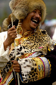 Tibetan man at the Horse Racing Festival or 'Heavenly Steed Festival' wearing endangered wild leopard cat skins, Zhongdian, Deqin Tibetan Autonymous Prefecture, Yunnan Province, China 2006  -  Pete Oxford