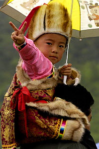 Child in traditional dress making V sign at the Horse Racing Festival or 'Heavenly Steed Festival' which takes place on the 5th and 6th days of the fifth lunar month. Zhongdian, Deqin Tibetan Autonymo...  -  Pete Oxford