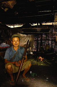 Black Lisu ethnic minority man sitting next to fire with crossbow - used to hunt wild animals that live in the hills near Fulong, Nujiang Prefecture, Yunnan Province, China 2006  -  Pete Oxford