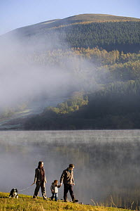 Family walking alongside Talybont reservoir in the Autumn, Brecon Beacons National Park, Powys, Wales  -  Nick Turner