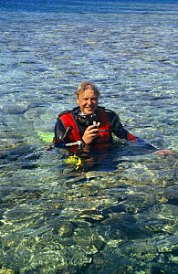 "Sir David Attenborough in scuba diving equipment on location for BBC television series ""Private Life of Plants"", early 1990s. Heron Island, Great Barrier Reef, Australia - NEIL NIGHTINGALE"