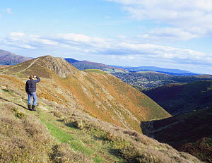 Hiker admiring the view of Devil's Mouth, Long Mynd SSSI, Shropshire Hills AONB, UK  -  Will Watson