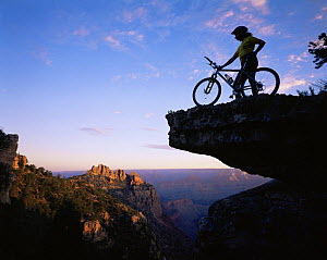 Mountain Biker stood on a ridge at sunrise overlooking the Grand Canyon, Grand Canyon NP, Arizona, USA  -  Jack Dykinga