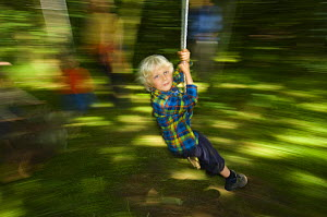 Young boy swinging through the forest, Letham, Fife, Scotland, UK  -  Niall Benvie