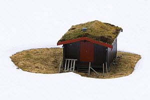 The case for house insulation - Cabin with melted snow around it illustrating the need for heat insulation, Norway 2007 - Niall Benvie