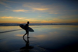 Surfer carrying surfboard up beach silhouetted at sunset, Sandymouth bay, Cornwall, UK  -  Ross Hoddinott