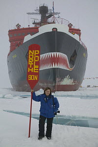 Photographer Sue Flood standing next to North Pole sign surrounded by water, on a tourist trip to the North Pole July 2007  -  Sue Flood