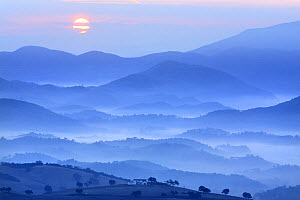 View of country house, fields and mountains with sun rising in the mist, Montellano, Seville, Spain - Jose B. Ruiz