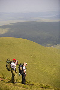 Walkers admiring the view at Llyn y Fan Fach, Brecon Beacons National Park, Powys, Wales  -  Nick Turner