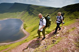 Walkers carrying backpacks hiking above Llyn y Fan Fach, a glacial cirque, beneath Black Mountain in the Brecon Beacons National Park, Powys, Wales  -  Nick Turner