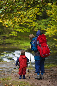 Adult walker carrying child in backpack with another child walking, in waterfall country along the Nedd Fechan, Brecon Beacons National Park, Powys, Wales  -  Nick Turner