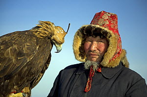 Portrait of Kazakh hunter with his Golden eagle, the Altai mountains of Xinjiang Province, north-west China. February 2007  -  George Chan