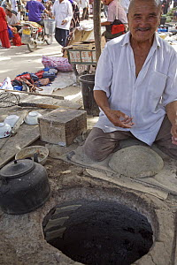 A man in Hotan City making bread in a muslim part of Xinjiang Province, north-west China. July 2006  -  George Chan
