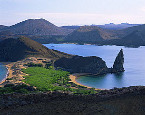A view across Bartolome Island and Pinnacle Rock, with Santiago Island in the background, Galapagos  -  Jack Dykinga