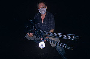 Ian McCarthy, cameraman, in bat cave wearing mask to protect him from fungal spores that grow on bat guano. - NIGEL MARVEN