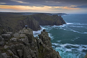 A lone photographer captures the rugged Cornish coastline, Land's End, Cornwall, UK  -  Adam Burton