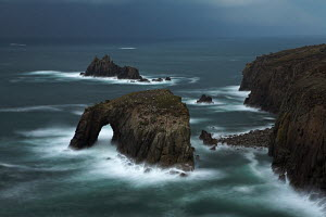 Stormy evening at Enys Dodnan Arch and the Armed Knight rock, Land's End, UK  -  Adam Burton
