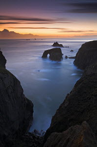 Twilight over the Enys Dodnan Arch and the Armed Knight rock, Land's End, Cornwall, with Longships lighthouse in the distance, UK - Adam Burton