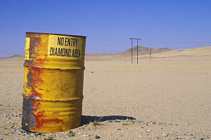 An old barrel at the diamond area border being used as a sign post warning people not to enter, Namib desert, Namibia  -  Jouan & Rius