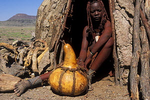 Himba woman at hut entrance, Kaokoland, Namib desert, Namibia  -  Jouan & Rius