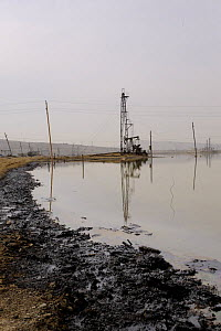 Oil Well and beam pump with pollution in subsidence lagoon, Baku, Azerbaijan, February 2008  -  Graham Eaton