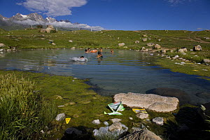 People bathing in hot spring in the mountains, with discarded rubbish, Dargye, Sichuan, Tibet - Dr. Axel Gebauer