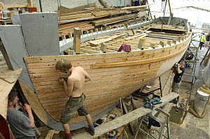Shipwrights fairing the hull of Bristol Channel Pilot Cutter ^Morwenna^. RB Boatbuilding, Underfall Yard, Bristol Floating Harbour, England. July 2008  -  Rob Cousins
