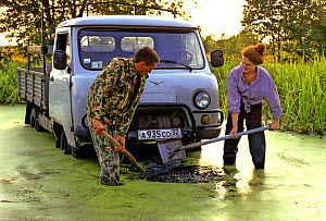 Igor Shpilenok, photographer and conservationist, and his wife Laura Williams digging truck out of mud and water, Bryansk province, Russia - Igor Shpilenok