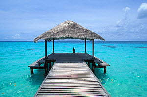 Woman sitting on end of covered pier in the Maldives, Indian Ocean  -  Benoit Stichelbaut