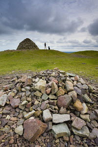 Stone cairns and person walking dog  at Dunkery Beacon, Exmoor National Park, Somerset, England - Adam Burton