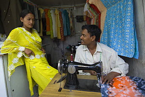 Tailor and woman with sewing machine in street market of Sombare, West Sikkim, India October 2007 - Bernard Castelein
