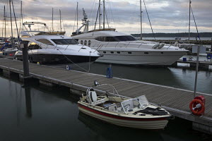 Luxury yachts and small motorboat moored at the quayside in Poole, Dorset, England - Adam Burton