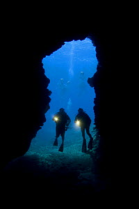 Divers with torches silhouetted at the entrance to First Cathedral cave off the Island of Lanai, Hawaii. August 2007. Model released  -  David Fleetham